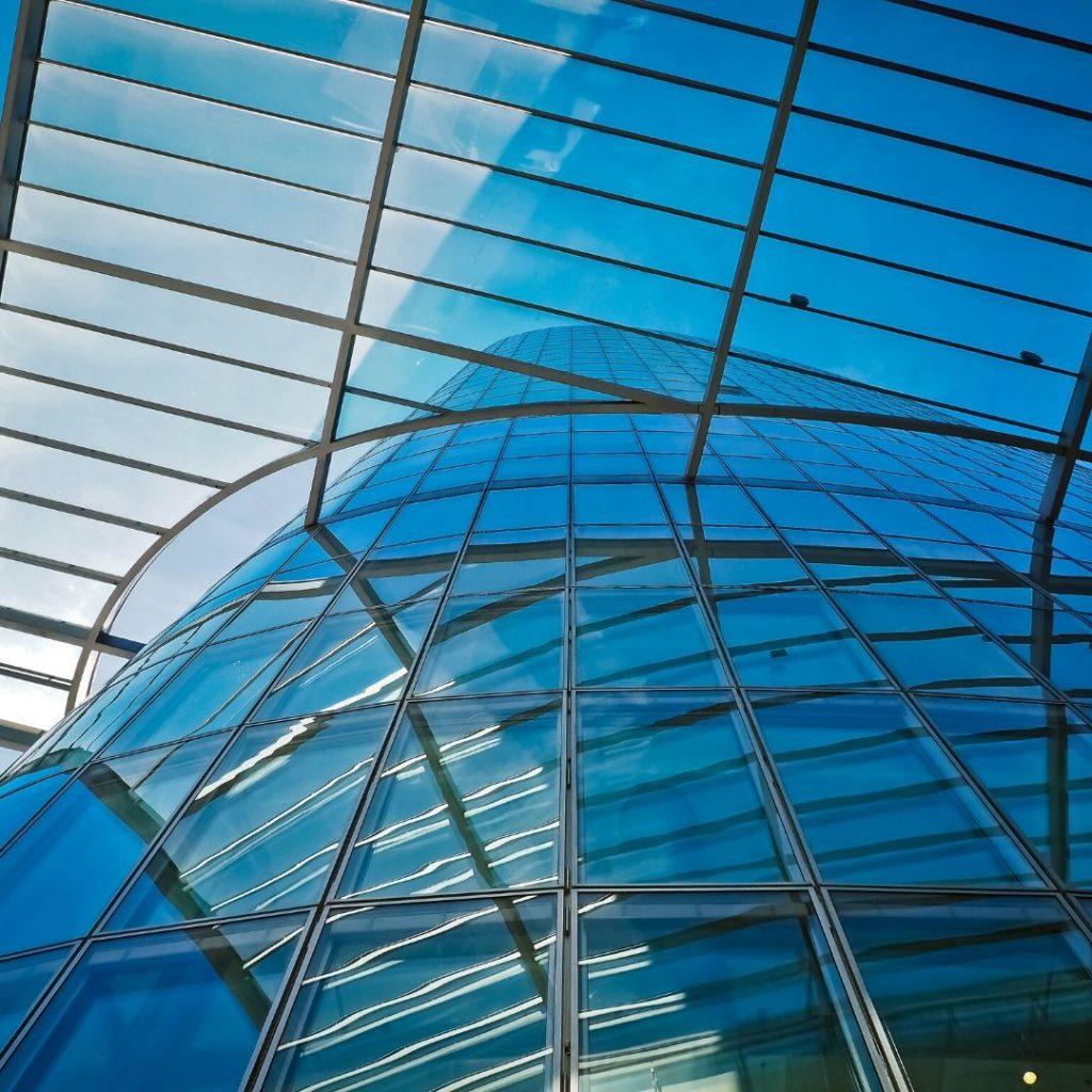 Trabajos de vidriería con cubierta de cristal unida a fachada acristalada